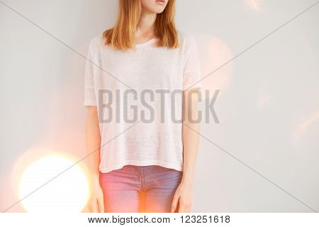 Woman Wearing White Blank T-shirt  Standing On The Background Of A Wall, Flare Light