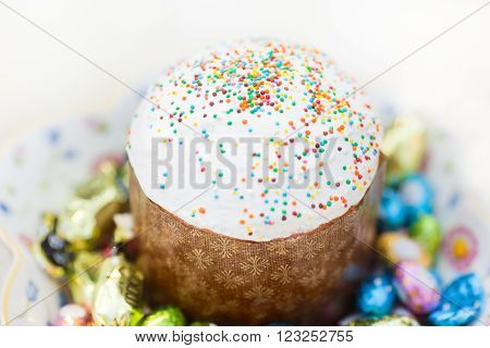 Easter cake and Easter eggs and candies over white background. Selective shallow focus