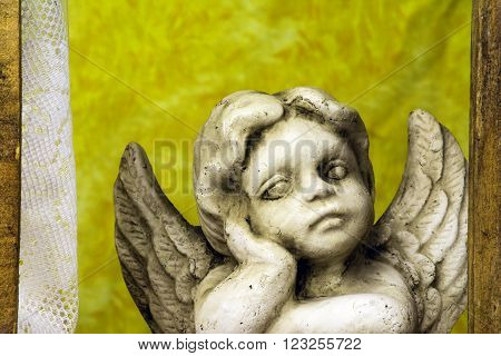 child angel looking out wood frame window with lace curtains and yellow background