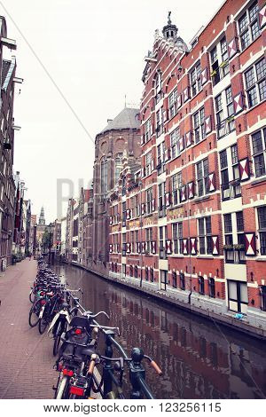 AMSTERDAM; THE NETHERLANDS - AUGUST 16; 2015: View on Oudezijds Kolk canal in Amsterdam building Verf en Vernis Fabriek H.Vettewinke in Amsterdam. Amsterdam is capital of the Netherlands on August 16; 2015.