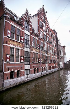 AMSTERDAM; THE NETHERLANDS - AUGUST 18; 2015: View on Oudezijds Kolk canal in Amsterdam building Verf en Vernis Fabriek H.Vettewinke in Amsterdam. Amsterdam is capital of the Netherlands on August 18; 2015.
