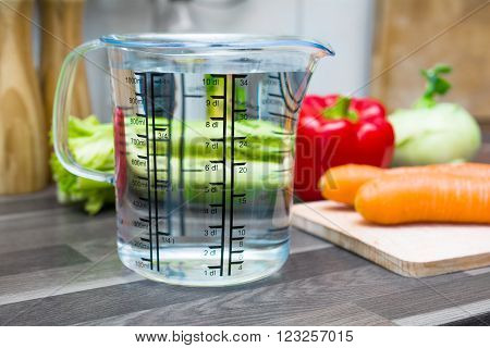 1 Liter / 1000ml / 10dl Of Water In A Measuring Cup On A Kitchen Counter With Vegetables