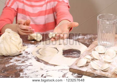 girl sculpts dumplings the dough is in the hands of a child
