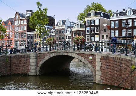 AMSTERDAM THE NETHERLANDS - AUGUST 18 2015: View on Prinsengracht from Spiegelgracht. Street life Canal pedestrians and bicycle in Amsterdam. Amsterdam is capital of the Netherlands on August 18 2015.