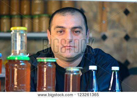 BAKU, AZERBAIJAN - MAY 4 2014  Honey seller at a Baku market. Man at popular market in central Baku, the capital city, sitting behind jars of home produced honey