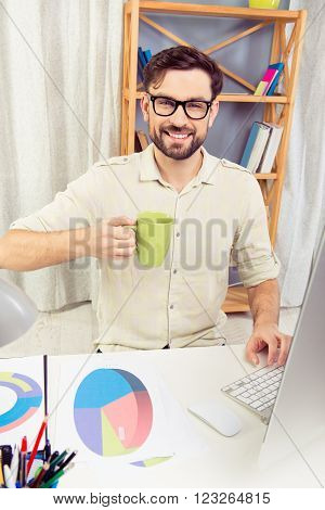 Young Businessman Sitting At The Table And Holding Cup Of Coffee