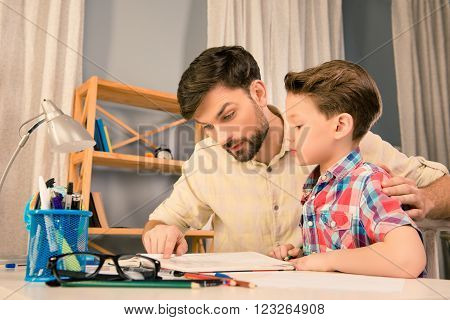 Father and son sitting at the table and reading interesting story