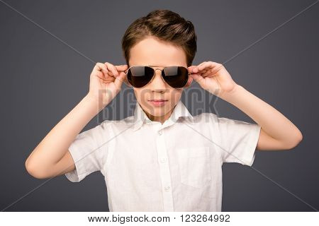 Stylish Handsome Little Schoolboy Touching His Glasses