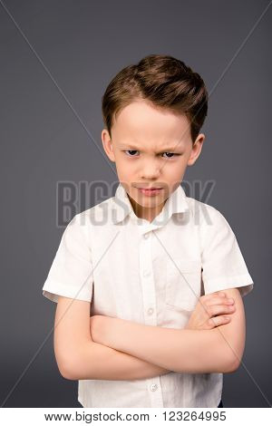 Portrait Of Cute Child Grimacing With Crossed Hands