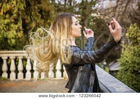 Side view of young woman standing near parapet with her hair flying in the air and outstretched arms