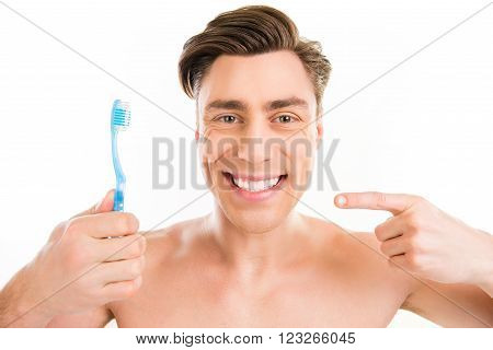 Toothy Happy Young Man Pointing On Blue Toothbrush