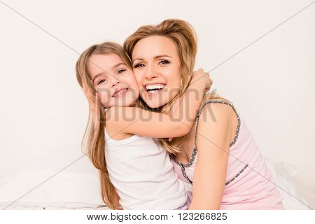 Close Up Portrait Of Little Girl Smiling And Huging Her Mom