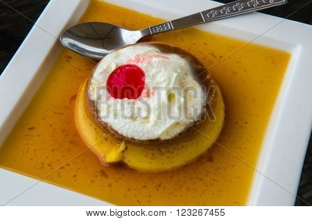 Caramel Custard, Custard Pudding with Cream on a white plate.