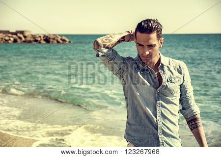 Three Quarter Shot of a Handsome Athletic Young Man in Trendy Attire, on a Beach in a Sunny Summer Day, Looking At Camera against Blue Sky Background.