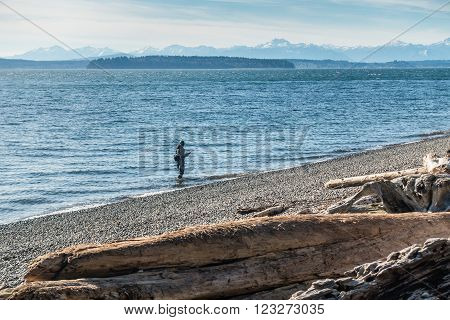 A view of a fisherman with the Olympic Mountains.