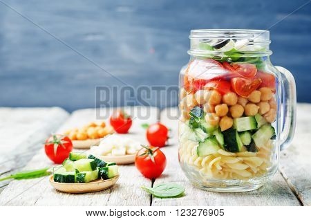 Pasta chickpeas cucumber tomatoes spinach goat cheese salad in a jar.