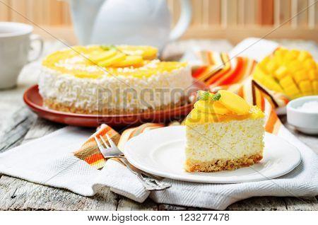 creamy mango mousse cake on a white wood background