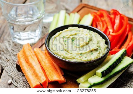 eggplant white bean dip with vegetables on wooden background