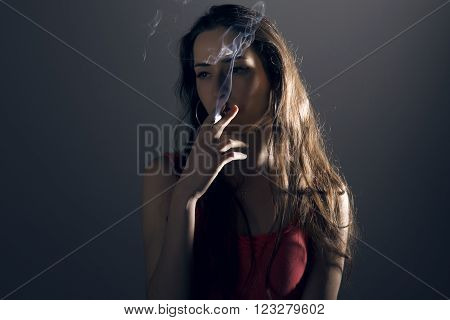 Beautiful young woman smoking a cigarrette inhaling over grey background.