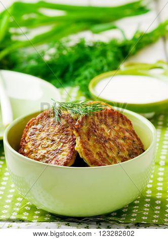 vegetable marrows fritters with sour cream on a green plate.