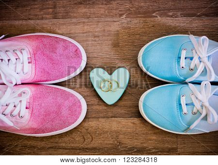 heart wedding rings and shoes on a wooden background