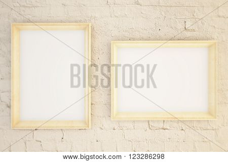 Two blank picture frames hanging on a beige brick wall. Mock up 3D Render
