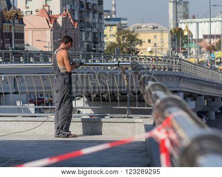 Kiev, Ukraine - September 18, 2015: Worker in overalls polish stainless steel handrail