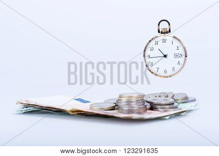 pocket watch with euro banknotes and coins, still life