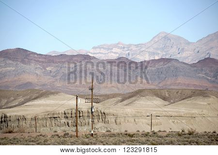 A radio mast and an electric pole standing in the desert in front of the slopes of a mountain range.