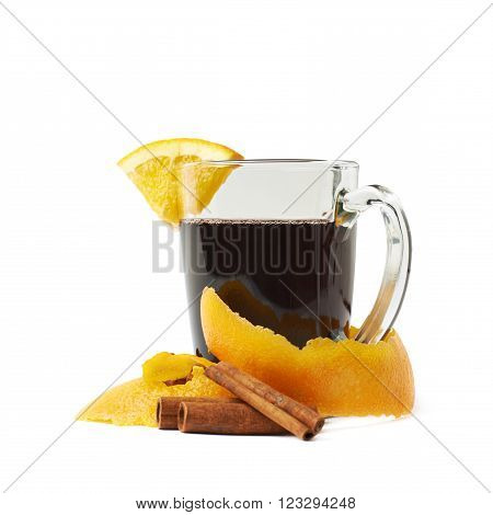 Glass of mulled wine decorated with the cinnamon sticks, peels and slice of orange, composition isolated over the white background