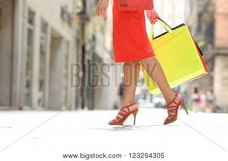 Side view of a shopper woman legs walking with shopping bags in a commercial street
