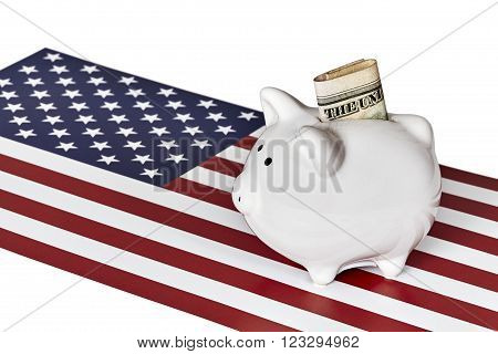 White ceramic piggy bank with paper currency in slot on bank with an American flag isolated on white