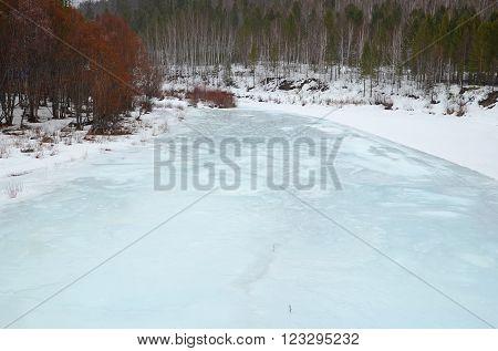 Irkutsk Region, Russia -March,20 2016: Icebound river on a cloudy spring day in the village. Irkutsk Region Russia