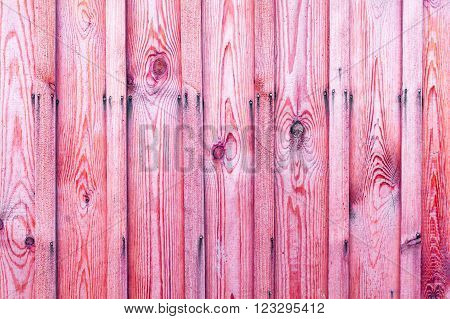 A fragment of a wooden fence. Wooden boards as a background with copy space. Wooden rustic wood boards background texture pink.