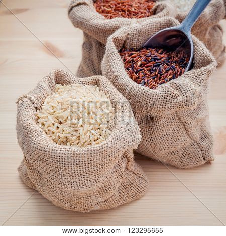 Mixed whole grain traditional thai rices best rices for healthy and super food in hemp sacks bag setup on wooden background.