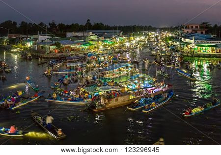 Soc Trang, Vietnam - February 3rd, 2016: Landscape dawn on the river floating market with the busy night boats lights twinkling in the night transporting agricultural goods to trade in preparation for this Lunar New Year in Delta water Soc Trang, Vietnam