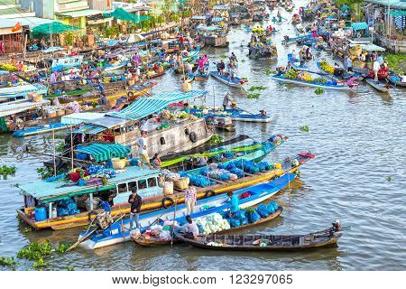 Soc Trang, Vietnam - February 3rd, 2016: Bustling produce market in the morning sun on the river with hundreds of boats gathered transporting fruit, flowers, vegetables traded on the confluence of the river culture water Soc Trang, Vietnam