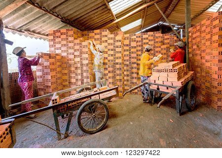 Vinh Long, Vietnam - February 5th, 2016: The group of workers is ranked terracotta tiles in the warehouse just a neat way to sell in the morning at brick villages in Vinh Long, Vietnam