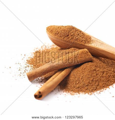 Pile of cinnamon powder with the wooden spoon and raw bark sticks on top of it, composition isolated over the white background