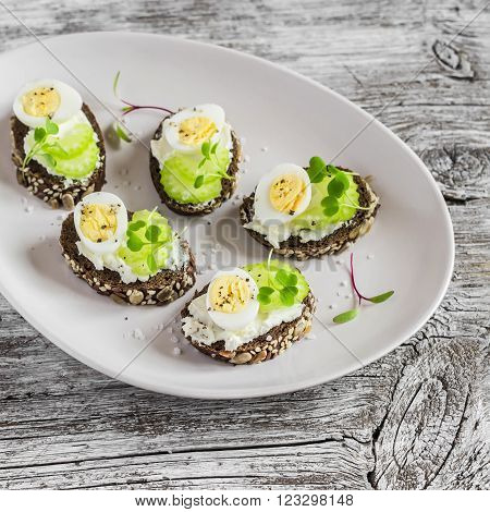 Open sandwiches with cream cheese quail eggs and celery.
