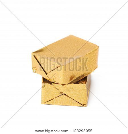 Pair of bouillon stock broth cubes wrapped in golden foil, composition isolated over the white background