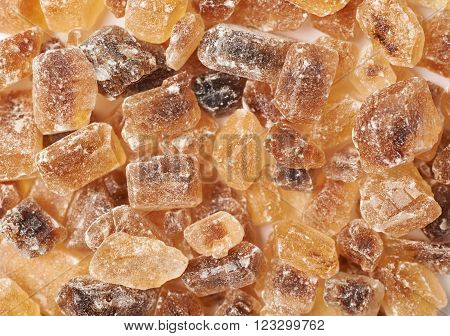 Surface coated with multiple large brown rock sugar crystals as a background composition ** Note: Shallow depth of field