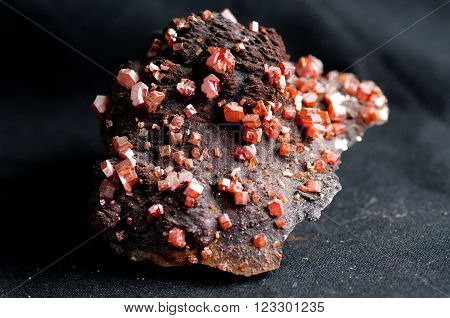 red vanadinite crystal mineral sample on metamorphic rock