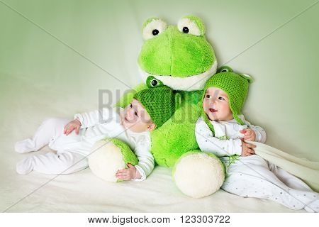 two cute six month old babies lying in frog hats with a soft toy