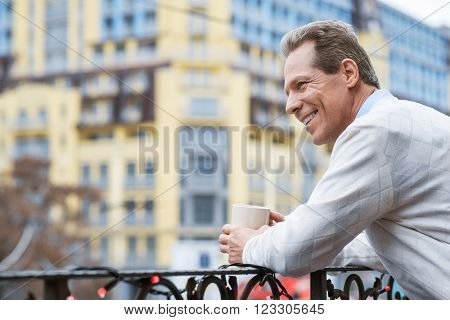 Get some rest. Cheerful man holding cup and resting while standing on the balcony