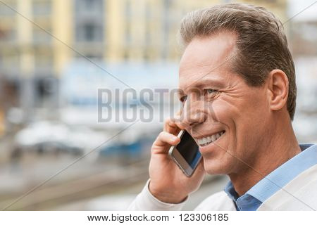 Modern way of life. Content positive man holding mobile phone and talking on it while expressing joy