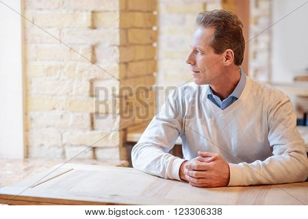 Let me think. Relaxed pleasant man holding hands in fists and looking in the window while sitting at the table