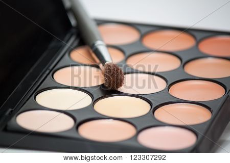 makeup palette with brush on white background