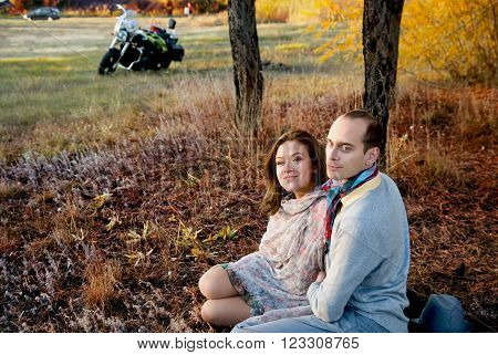 Guy and girl in woods in autumn. Enamored couple sitting side by side on grass and looking away. In background, a motorcycle and a car
