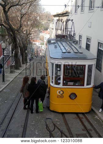 Lisbon Portugal - March 17th 2016. Yellow Lisbon Fenicular tram called Gloria loading passengers